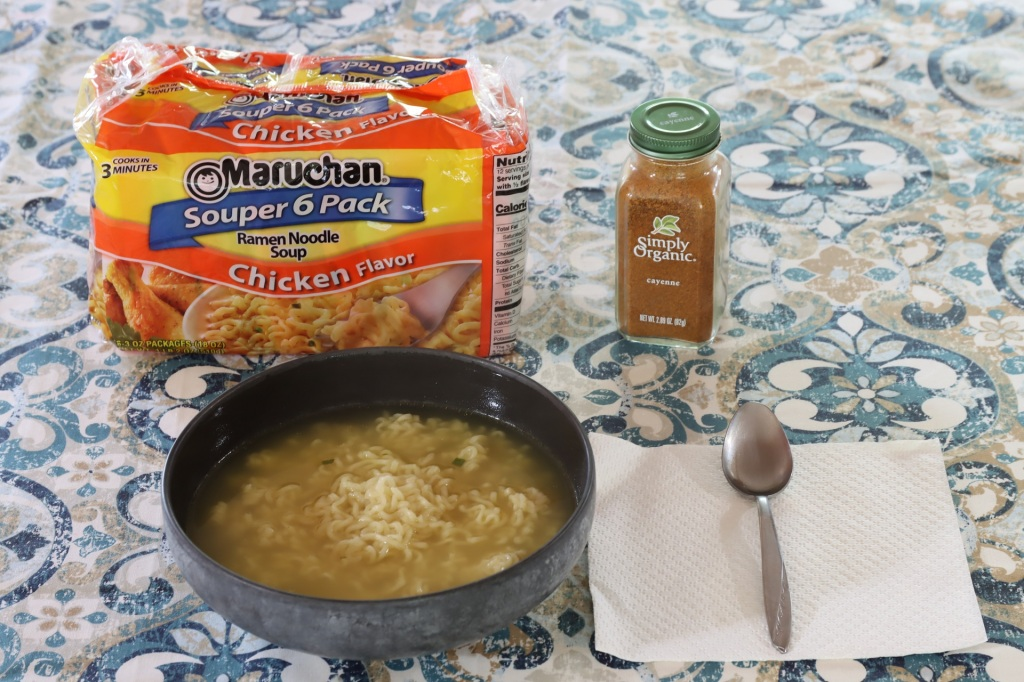 Bowl of ramen and bottle of spice